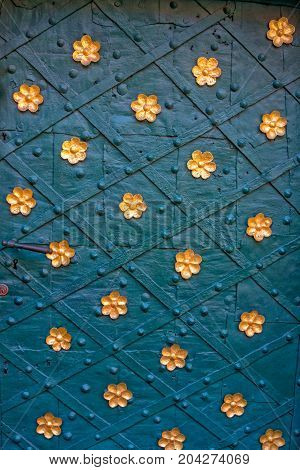 Ancient metal door with rivets, decorated with golden colored flowers