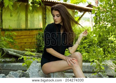 delicate slender girl sits on the rocks looks away and keeps hand hair
