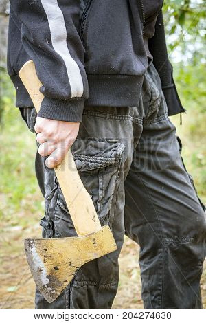 A man holds an ax in his hand while in the forest