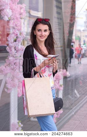 vertical portrait of joyous beautiful brunette that stands near the store with items and packages