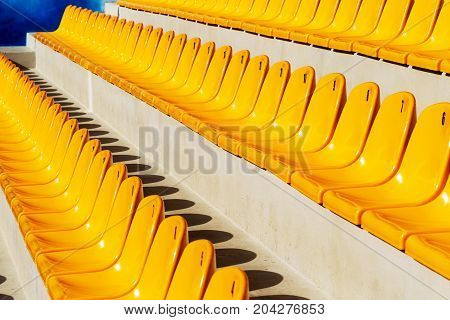Row Of Plastic Chairs. Empty Rows Of Yellow Chairs For The Audience As A Background For Creative Art