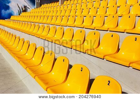 Row of plastic chairs. Empty rows of yellow chairs for the audience as a background for creative art design