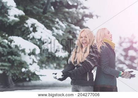 Twin Women Playing Snowballs In Forest On Snow Landscape