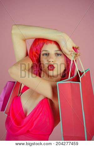 Girl wearing red wig and fashionable clothes. Woman with shopping bags. Fashion shopper making duck face on pink background. Sale and black friday. Holidays celebration concept.