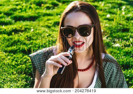 Happy fashion smiling Woman in sunglasses smoking vape on street,smoke smoker