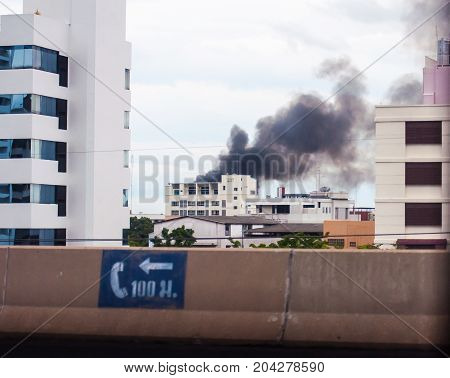 The Fire In The Community Of Smoke Floating High As Tall Buildings. View On The Bridge