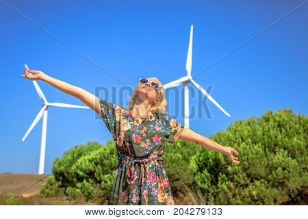 A blond caucasian happy woman with open arms enjoying in front of wind turbines rotating in Sagres, Algarve, Portugal. Alternative energy, renewable energy and environmental sustainability concept.