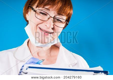 Woman doctor with braces on teeth writing prescription