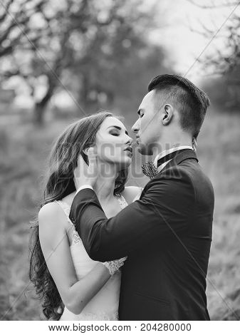 Beautiful bridal couple of young man embracing happy pretty woman outdoor