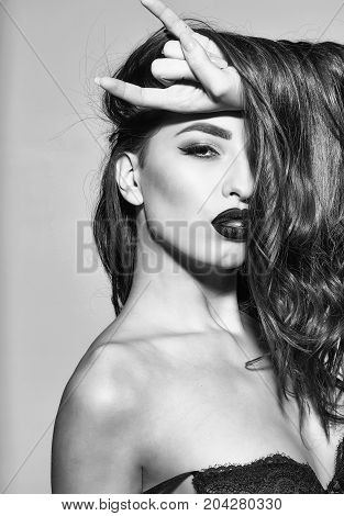 pretty woman or cute sexy girl with long curly brunette hair has red lips makeup on adorable face on grey background