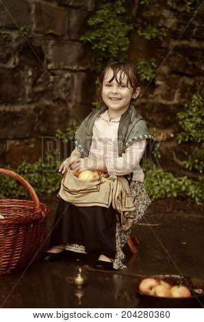 Little melancholy caucasian girl with a basket of apples. Little merchant