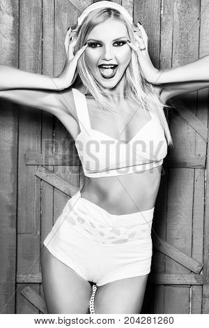 young woman or girl dj with blonde hair and red lips on pretty smiling sexy face in white bra with shorts and musical stereo headphones or headset in studio on wooden background