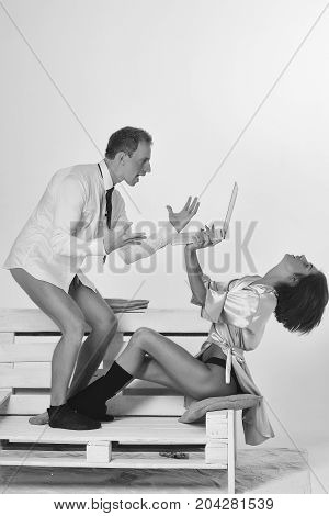 young couple of handsome amazed man or businessman and pretty woman or girl working on portable laptop or computer in shirt socks and tie sits on wooden bench isolated on white background