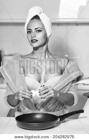 One sexual beautiful sensual female housewife in blue terry dressing gown and towel turban on head with bare shoulders standing in kitchen cooking breakfast from fried eggs in morning life vertical