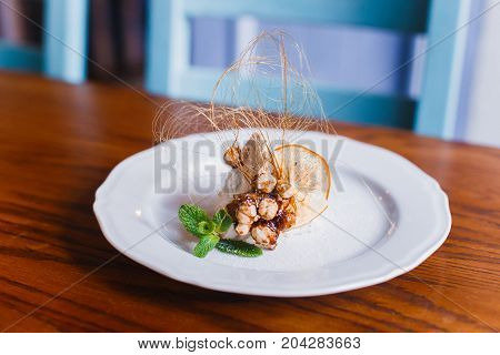 The close-up photo of the piece of ice cream with nuts, mint and decorated with dried orange placed on the wooden table