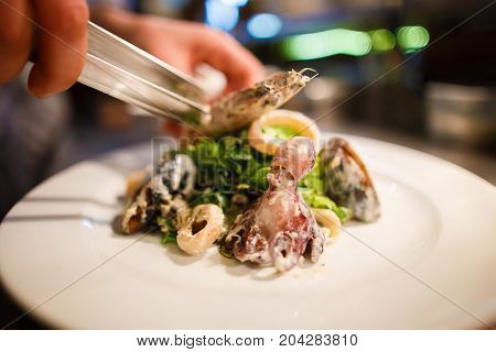 The side view of the chef cooking the seafood salad consisted of the lettuce, onion circles, mussels and octopus placed on the white plate