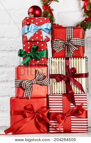 Stack of bright colorful giftboxes wrapped in paper and decorated with ribbons against wall with wreath.