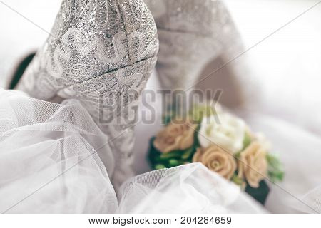 Close-up of textured lace surface of silver bridal high heels composed with veil and bouquet.