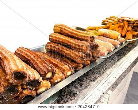 Churros on a market stall in a bakery shop. Sweet Famous Spanish dessert with chocolate sauce close up