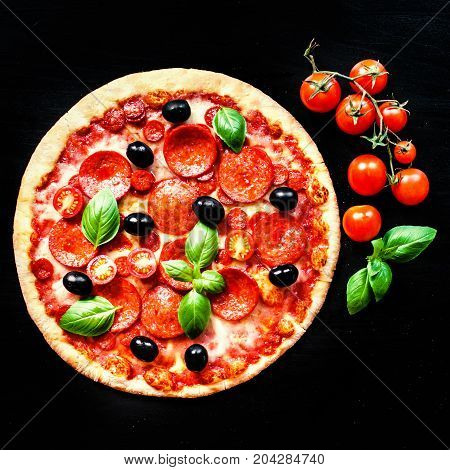 Freshly baked Pizza with Pepperoni Sausage and cheese in a rustic Italian style on dark background. Hot fresh pizza with meat and mozzarella cheese macro