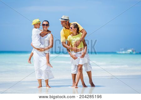 Family of four - father with his child having fun at the white sand beach