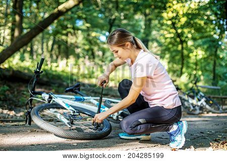A woman repairs wheel of a bicycle. The concept of cycling and a healthy lifestyle.