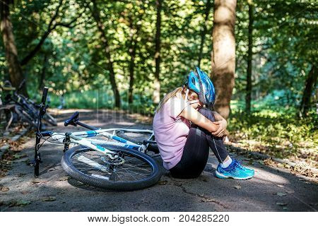 The woman fell from a bicycle in a helmet. Trauma. The concept of cycling and a healthy lifestyle.