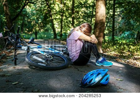 The woman fell from the bike. Trauma. The concept of cycling and a healthy lifestyle.