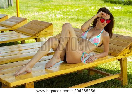 slender sexy girl in a bathing suit sunning on the beach on a sunny day