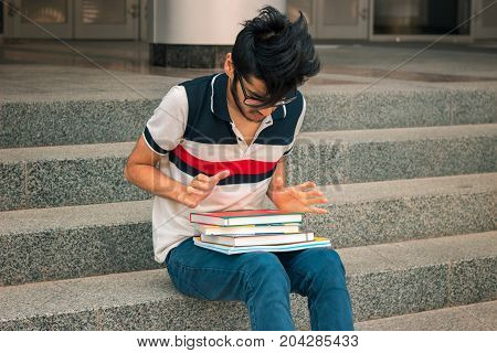 young student sits on the steps outside and looks at books
