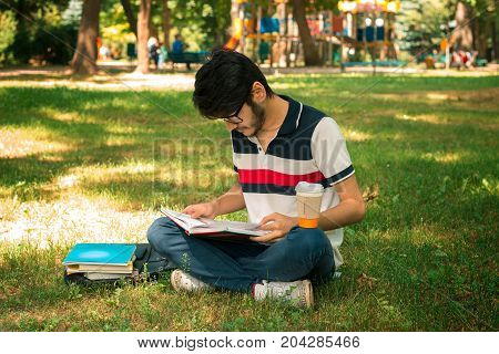 young charming guy reads a book in the Park on the grass