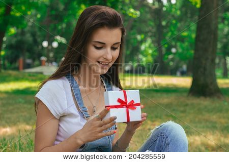 Portrait of a cute young girl who smiles and holds a small gift in the hands