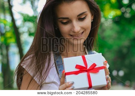 a close-up portrait of young charming girl with a gift in the hands