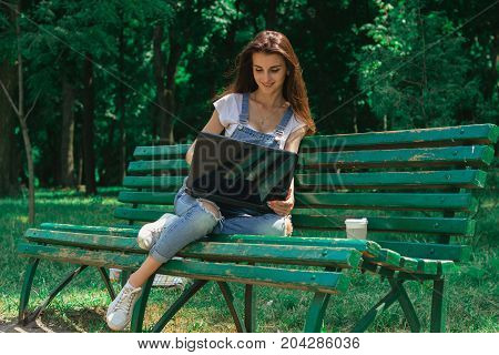 cheerful young girl sits on a bench and using a laptop outdoors