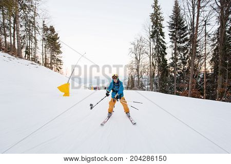 Man On Skis Moving Down The Mountain Slope And Taking Selfie With Stick On The Winter Ski Resort Rec