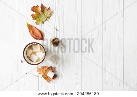 Fall still life with yellow leaves, coffe with marshmallows, autumn flat lay on white wooden background