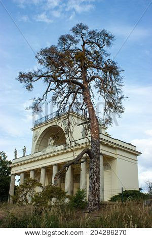 View on the Apollo temple in the Czech republic. On the background is blue sky with white clouds. A tall tree stands beside the temple.