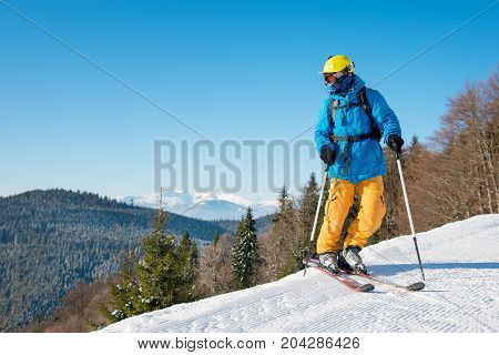 Shot Of A Professional Skier In Colorful Gear Skiing On Fresh Powder Snow In The Mountains On The Wi