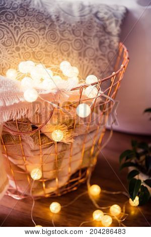 Cozy home interior decoration, metal basket with pillow, warm blanket and string lights on the floor, autumn room decor closeup
