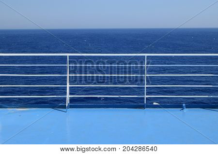 Railings on ferry boat cruise ship deck. Blue sea and sky summer travel background.