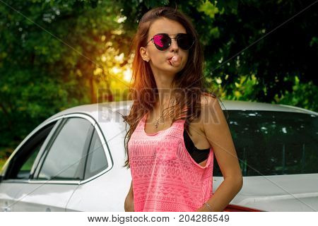 young glamour brunette in dark glasses with chewing gum in the mouth stands near the car close-up