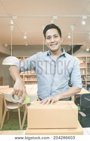 Young Asian Entrepreneur Packing Product Into The Box For His Customers After Received Order At Home