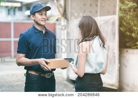 Handsome Young Asian Delivery Man Smiling And Holding A Cardboard Box While Waiting Beautiful Young