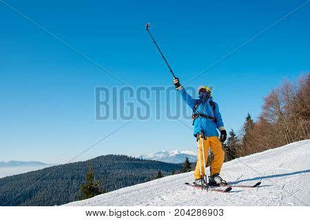 Full Length Shot Of A Professional Skier Taking A Selfie Using Selfie Stick Posing On The Slope. Blu