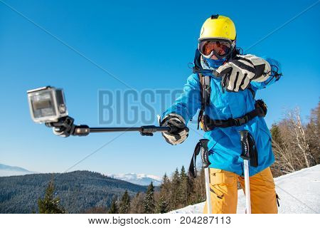 Horizontal Shot Of A Male Skier Having Fun Outdoors Taking A Selfie With Action Camera On A Monopod