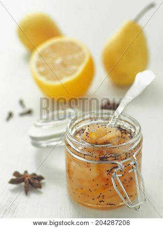 Pear jam in a jar upon white wooden table. Selective focus on the jar.