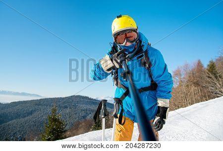 Shot Of A Man Skier Wearing Ski Equipment Taking A Selfie Using Monopod At The Winter Resort. Blue S