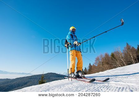 Full Length Shot Of A Skier Standing On Top Of A Mountain On A Sunny Winter Day Taking A Selfie With