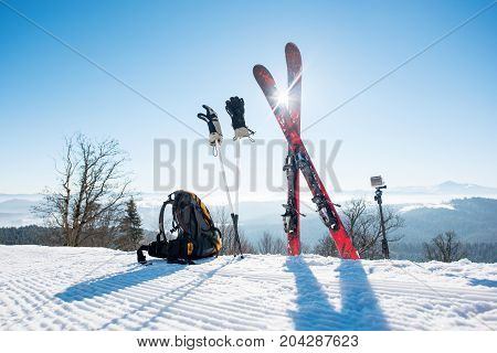 Shot of skiing equipment - skis backpack sticks gloves and action camera on monopod on top of the ski at ski resort in the mountains winter sports lifestyle extreme active concept
