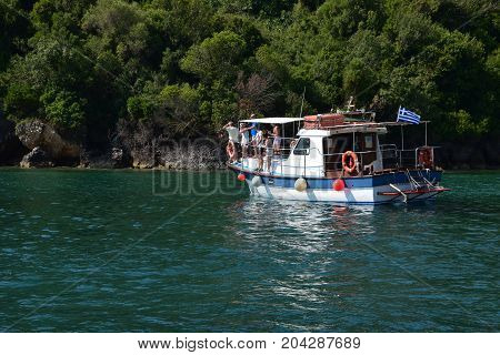 ZAKYNTHOS GREECE - JULY 5 2015: People on fishing boat have spotted a caretta sea turtle swimming in the shallows close to Keri beach in the national sea park of Zakynthos Greece.